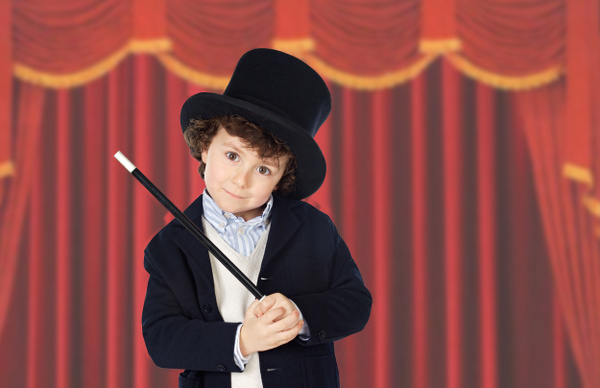 Adorable child dress of illusionist with hat and red curtains of background